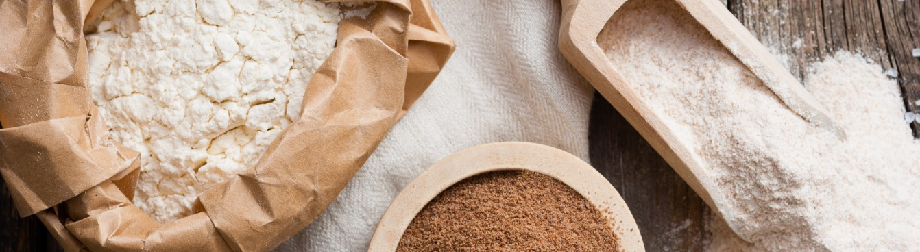 Powdered flour in paper bag with wooden scoop